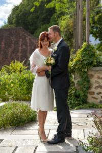 Hochzeitsfoto eines stehenden Braupaars draußen vor einem grünen Gartenhintergrund