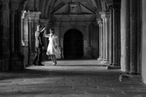 Schwarzweißfoto eines tanzenden  Hochzeitspaars in einem Säulengang