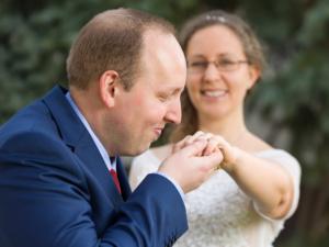 Foto eines jungen Hochzeitspaars wobei der Bräutigam die Hand der Braut küsst