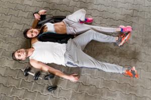 Paarfoto eines sportlichen Paars am boden liegend, mit Gewichten und Trainingsanzügen