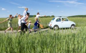 Familie, die auf einer Straße zwischen hohen Gräsern einem blauen Auto nachlaufen