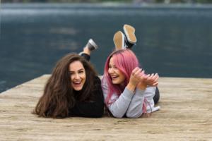 Foto von zwei Mädchen, die auf einem Steg liegen und sich anlachen