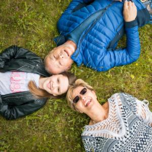 Familienfoto von Eltern mit einer jungen Tochter, die auf einer Wiese auf dem Boden liegen