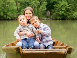 Familienfoto von einem Mädchen und zwei Burschen, die in einem Boot auf einem See sitzen