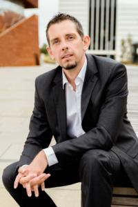 Businessportrait eines Mannes im schwarzen Anzug mit einem weißen Hemd sitzend draußen