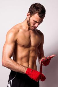 Portraits eines sportlichen jungen Mannes mit nacktem Oberkörper, der sich gerade die Hände bandagiert