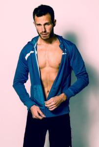 Portrait eines sportlichen Mannes mit einem blauen Sweatshirt vor einer weißen Wand im Studio