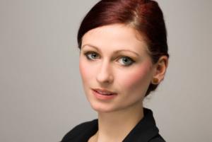 Businessportrait einer jungen Frau mit roten Haaren und einem schwarzen Blazer im Studio