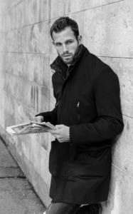Schwarzweiß Portraits eines zeitunglesenden Mannes in einem schwarzen Mantel an eine Wand gelehnt