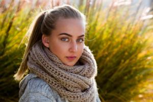 Portrait einer jungen Frau mit blonden langen Haaren und einem Schal im Freien vor gelben Gräsern