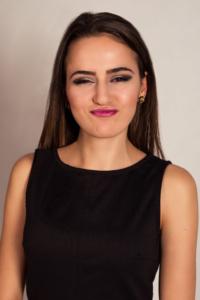 Portrait einer jungen Frau mit einem schwarzen Oberteil, langen schwarzen Haaren vor einer weißen Wand im Studio