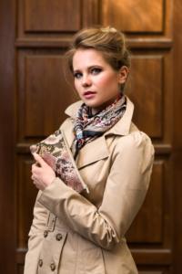 Portrait einer jungen Dame in einem hellbraunen Mantel vor einer dunkelbraunen Türe