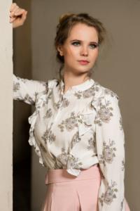 Portraits einer jungen Dame mit hochgesteckten Haaren, einer weißen Bluse mit Blumen und einem rosa Rock lehnend an einer Säule
