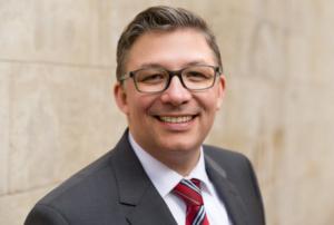 Portrait eines Mannes im grauen Anzug mit weißem Hemd und Krawatte vor einer braunen Wand