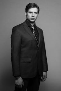Businessportrait eines Mannes im schwarzen Anzug vor einer grauen Wand im Studio
