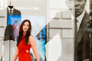 Portrait einer Frau in einem roten Kleid mit langen braunen Haaren vor einem Schaufenster