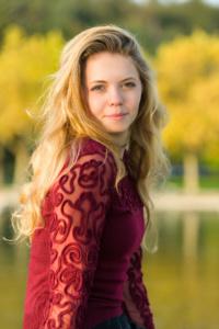Portrait einer jungen Frau mit blonden gelockten Haaren. die Frau sitzt draußen im hellgelben Sonnenschein