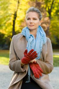Portrait einer Frau mit blonden Haaren, einem blauen Schal, einem braunen Mantel und roten Handschuhen. Die Frau steht vor einem herbstlichen Hintergrund