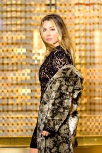 Portrait einer Frau mit blonden langen Haaren draußen. Die Frau hat ein schwarzes Kleid an und hat einen Pelzmantel umgeschlungen. Die Frau steht vor einem goldenen Hintergrund