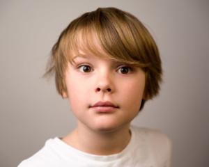 Portrait eines jugendlichen Bubens mit weißem T-Shirt und blonden Haaren