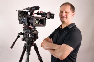 Businessportrait eines Kameramannes in einem schwarzen T-Shirt, stehend vor seiner Profikamera