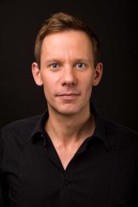 Businessportrait eines Mannes im schwarzen Hemd vor schwarzem Hintergrund