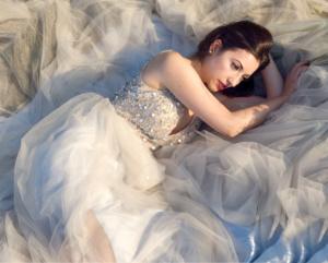 Portrait einer jungen Frau am Boden liegend mit braunen Haaren und einem weißen Kleid mit glitzernden Steinen