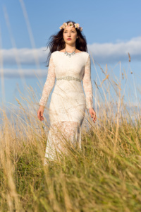 Portrait einer jungen Frau draußen auf einer Wiese in einem weißen Kleid