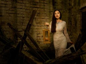 Bild einer Frau in einem weißen Kleid mit einer Laterne in einem verlassenen Haus mit Ziegeln und Holz