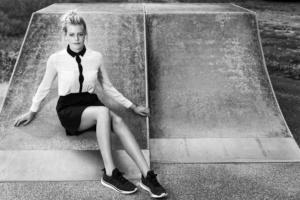 Portrait einer jungen Frau in einem scharzen Rock und mit einer weißen Bluse sitzend auf einer Skateboardrampe