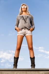 Portrait einer jungen Frau in einem sportlichen Gewand (kurze Hose, T-Shirt) vor einem blauen Himmel