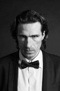 Schwarzweiß Portraits eines Mannes im Smoking mit Fliege vor einem dunklen Hintergrund