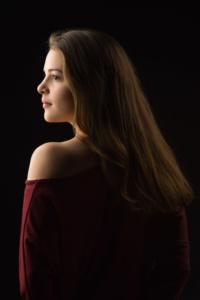 Portrait einer jungen Frau mit langen Haaren und rotem Oberteil im Studio.