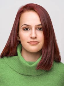 Portraits einer jungen Frau mit rotbraunen glatten Haaren mit einem grünen Pullover vor einerm weißen Hintergrund