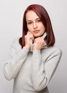 Portrait einer jugen Frau im Studio vor einem weißen Hintergrund. Die Frau hat einen grauen Pullover an und hat rotbraune Haare