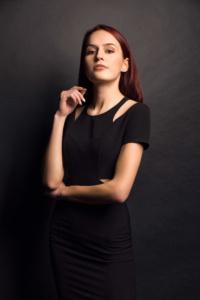 Portrait einer jungen Frau in einem schwarzen Kleid vor einer schwarzen Wand und im Studio
