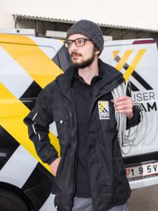 Portrait eines jungen Elektronmonteurs in Arbeitskleidung vor einem Lieferwagen
