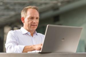 Businessportrait eines Mannes in einem weißen Hemd vor einem Notebook sitzend