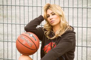 Portrait einer Frau mit einem Basketball und einem Sweatshirt sitzend im Freien auf einem Basketballplatz