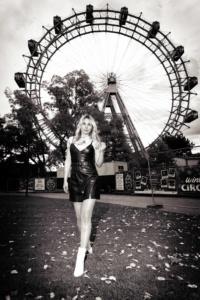 Schwarzweiß Portrait einer stehenden Frau in einem dunklen Kleid vor dem Wiener Riesenrad