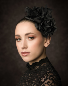 Portrait einer hübsch geschminkten, jungen Frau mit schwarzen Haaren und eleganten Blumen in den Haaren vor einem dunklen Hintergrund